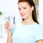 Woman holds a glass with water